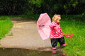 Cute Little Girl With Umbrella In Raincoat And Boots Royalty Free Stock Images - 66390879