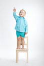 Boy On Chair And Pointing His Finger Up Stock Photography - 66411082