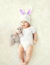 Happy Sweet Baby In Knitted Hat With A Rabbit Ears And Teddy Bear On Bed Stock Photos - 66435443