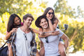 Hip Men Giving Piggy Back To Their Girlfriends And Taking Selfie Royalty Free Stock Photography - 66435817