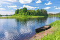 View On River With Island And Wooden Boat Laid Up On Riverbank Stock Photo - 66497430
