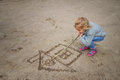 Little Girl Draws In The Sand Stock Photo - 66836060