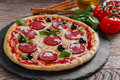 Pizza With Salami Tomato And Cheese On A Black Stone Stock Images - 66902204