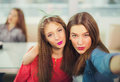 Two Girls Pouting While Taking A Selfie Photo On Mobile Phone Stock Photography - 66988782