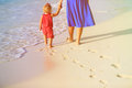 Mother And Daughter Walking On Beach Leaving Footprint In  Sand Stock Photo - 66991030