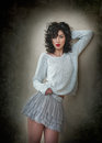 Charming Young Curly Brunette Woman In Lace Short Skirt And White Blouse Leaning Against Wall. Sexy Gorgeous Young Woman Stock Image - 67044931