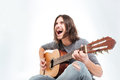 Happy Young Man With Long Hair Playing Guitar And Singing Royalty Free Stock Photography - 67087887