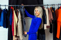 Attractive Young Blonde Woman Smiling And Choosing Clothes In St Stock Photos - 67103753