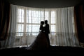 Silhouette Bride And Groom Kissing In Front Of Narrow Window Stock Images - 67174564