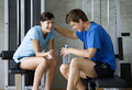 Two Friends Sitting In A Gym Royalty Free Stock Image - 67224256