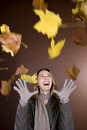 A Mid Adult Woman Smiling At Falling Autumn Leaves Stock Images - 67250984