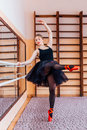 Ballerina Wearing Black Tutu Doing Exercise In Training  Hall. Stock Image - 67254041