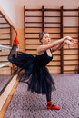 Ballerina Wearing Black Tutu Doing Exercise In Training  Hall. Royalty Free Stock Photography - 67255637