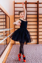 Young Smiling Ballerina Wearing Black Tutu Doing Exercise In Training  Hall Stock Images - 67259404