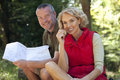 A Mature Couple Sitting Outdoors Resting, Man Holding A Map Royalty Free Stock Photo - 67263675