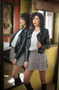 Young Woman In Black Leather Jacket And Gray Short Tutu Skirt Looking Into A Large Mirror. Beautiful Curly Dark Hair Girl Posing Royalty Free Stock Image - 67370466