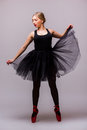 Young Blonde Ballerina Girl Dance And Posing In Black Tutu And Ballet Shoes On Grey Background. Stock Image - 67439401