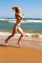 Little Curly Cheerful Girl Runs Along The Shore Of The Ocean On Stock Photography - 67456682