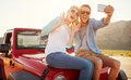 Couple On Road Trip Sit On Convertible Car Taking Selfie Stock Photography - 67525142