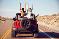 Rear View Of Friends On Road Trip Driving In Convertible Car Royalty Free Stock Images - 67525229