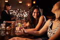 Female Friends Enjoying Night Out At Cocktail Bar Royalty Free Stock Photo - 67525905