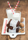 Chocolate Brownie Slices Wrapped In Paper And Tired With Rope, Glasses Of Milk, Stripe Straws, Walnuts On White Ceramic Royalty Free Stock Images - 67598949
