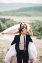 Beautifull Wedding Couple Kissing And Embracing Near The Shore Of A Mountain River With Stones Stock Images - 67632904
