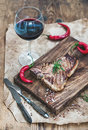 Cooked Meat T-bone Steak On Serving Board With Roasted Tomatoes, Chili Peppers, Fresh Rosemary, Spices And Glass Of Red Stock Photo - 67690850