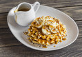 Waffles With Banana Slices, Nuts And Caramel Sauce Royalty Free Stock Images - 67931759