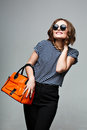 Fashionable Woman With An Orange Bag And Large Round Sunglasses. Stock Image - 67968171