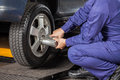Mechanic Screwing Car Tire With Pneumatic Wrench Stock Photography - 68025582