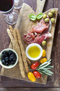 Cured Meat On A Wooden Cutting Board With Red Tomatoes, Olives A Stock Photo - 68049380