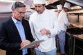 Male Restaurant Manager Writing On Clipboard While Interacting To Head Chef Stock Photo - 68256870