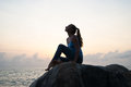 The Beautiful Girl Sitting On Stones And Looking In A Distance, The Girl At Sunset To Meditate In Silence, Beautiful Body. Concept Royalty Free Stock Images - 68331179