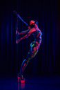 Female Pole Dancer In Bright Neon Colours Under Ultraviolet Royalty Free Stock Image - 68392766