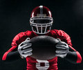 American Football Player Posing With Ball On Black Background Stock Photo - 68479670