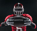 American Football Player Posing With Ball On Black Background Royalty Free Stock Photo - 68480905