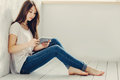 Sitting Near The Wall And Looks In Tablet Royalty Free Stock Image - 68483826