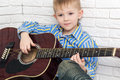 Thoughtful Little Boy Sitting And Playing The Guitar Stock Image - 68666581