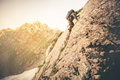 Man Traveler With Big Backpack Climbing On Rocks Royalty Free Stock Images - 68686599