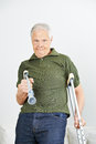Senior Man Fighting With Crutches Stock Images - 68693144