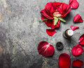 Red Roses Flowers And Petals And Bottle Of Essential Oil On Gray Vintage Background, Top View Royalty Free Stock Photo - 68872385