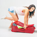 Young Woman Packs Her Things, Clothes At Full Luggage Stock Photo - 68990580