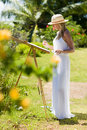 Slim Painter Woman In White Dress And Hat In Tropical Environment Stock Images - 69021504