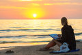 Young Girl Sitting On The Beach, Drawing On A Sheet Of Watercolor Sunset And Looked At The Setting Sun Stock Photo - 69051510