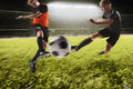 Two Soccer Players Kicking A Soccer Ball Royalty Free Stock Photo - 69077355