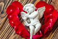 Closeup View Of Beautiful Cupid With The Trumpet, Angel Decorative Figurine Near Red Rose Petals On Wooden Background. Royalty Free Stock Images - 69235319