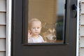 Baby And Pet Dog Waiting At Door Looking Out Window Stock Image - 69371901