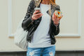Portrait Of A Beautiful Young Sexy Woman Eating A Donut, Looks At Her Smart Phone On The Street European City. Body Part. Outdoor. Stock Images - 69397014