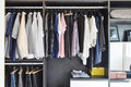 Closet With Row Of Cloths Hanging In Black Wardrobe Stock Images - 69549444
